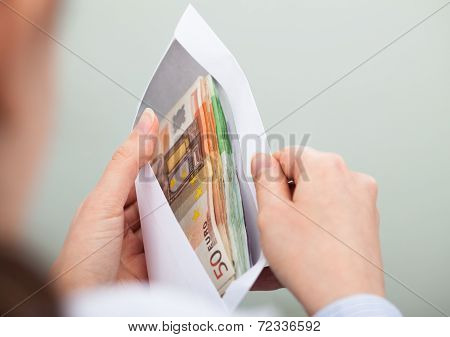 Person Checking Out Envelope With Cash