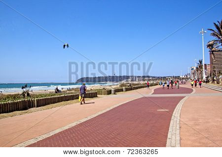 People Walking Along Paved Promenade On Beach Front