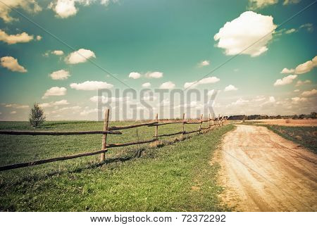 Sunny Day In Countryside. Empty Rural Road Going Through Summer Landscape Under Blue Cloudy Sky