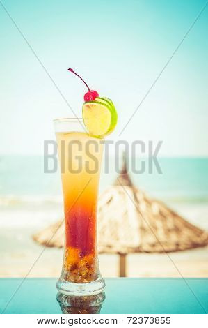 Long Island Cocktail With Fruits Decoration At Tropical Ocean Beach With Umbrella