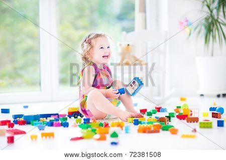 Adorable Laughing Toddler Girl Playing With Colorful Blocks Sitting On A Floor In A Sunny Bedroom