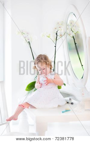 Beautiful Toddler Girl Playing With Cosmetics Sitting On Her Mother's White Dresser With A Mirror