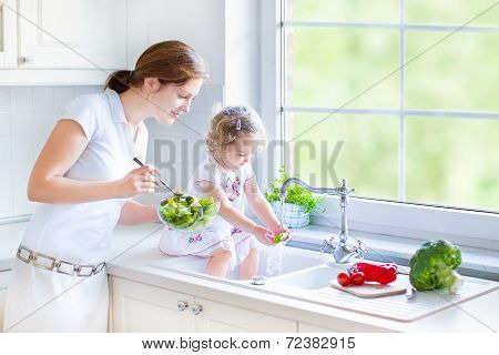 Young Beautiful Mother And Her Cute Curly Toddler Daughter Washing Vegetables Together In A Kitchen