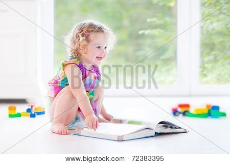 Cute Toddler Girl With Blond Curly Hair Reading A Book Sitting On A Floor Reading A Book