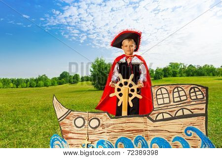 Boy as pirate stands on ship and holds the helm