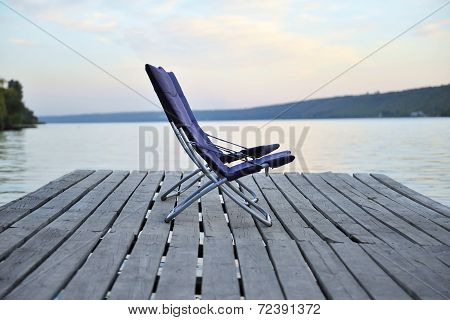 Two Chairs On A Wooden Platform On The River