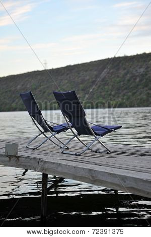 Two Folding Chairs On A Wooden Platform On The River