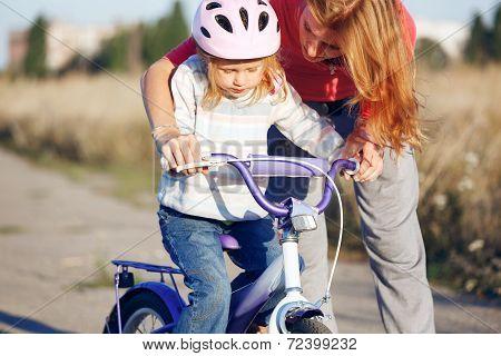 Redhead Girl In Helmet Learning Riding Bike.