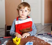 stock photo of ginger bread  - Adorable boy baking ginger bread cookies for Christmas in home - JPG