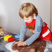 image of ginger bread  - Adorable little boy baking ginger bread cookies for Christmas in home - JPG