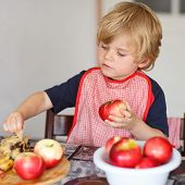 pic of pie-in-face  - Happy little kid boy helping and baking apple pie in home - JPG