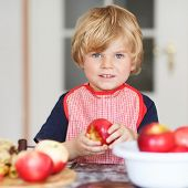 image of pie-in-face  - Adorable little child helping and baking apple pie in home - JPG
