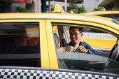 pic of leaving  - Asian man working as taxi driver in yellow car with female client paying cash and leaving - JPG