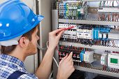 pic of multimeter  - Side view of male technician examining fusebox with multimeter probe - JPG