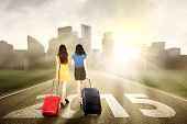 picture of carry-on luggage  - Rear view of two women carrying suitcase walking on the road towards the future 2015 - JPG