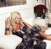 image of coat  - fashion photo of beautiful sexy woman with blond hair in lingerie and fur coat lying on bed with glass of champagne - JPG