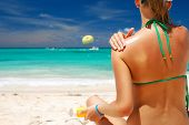 picture of sunbathing woman  - Tan woman applying sun protection lotion  - JPG