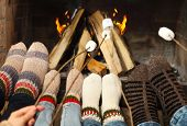 picture of early-man  - Feet of the family warming at a fireplace with marshmallows on sticks - JPG