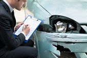 pic of clipboard  - Side view of writing on clipboard while insurance agent examining car after accident - JPG