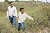 African-American boy walking with father along sand dunes