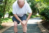 pic of knee  - Closeup portrait older man in white shirt gray shorts standing on paved road in severe knee pain isolated trees outside outdoors background - JPG
