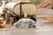 picture of tank truck  - large truck pulling a water tank spraying for dust control at a log yard at a lumber processing mill that specializes in small logs - JPG