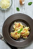 picture of carbonara  - Pasta Carbonara in dark plate on a white wooden table