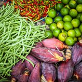 stock photo of lime-blossom  - Fresh beans banana flowers lime and chili peppers for sale at asian market - JPG