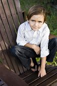 Portrait of a cute little boy on an adirondack chair