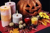 foto of centerpiece  - Happy Halloween party table centerpiece with orange glitter jack-o-lantern pumpkin with lit candles and autumn Fall leaves nuts and berries on black tablecloth.