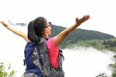 picture of emei  - woman hiker open arms at peak of emei mountain  - JPG