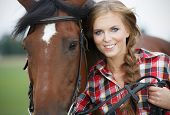 foto of auburn  - Beautiful smiling woman with blond hair with a horse - JPG