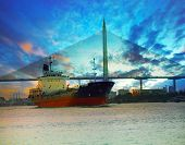 stock photo of fuel tanker  - tanker ship in river against beautiful bridge with twilight sky of urban scene use for marine transport and freight industry business - JPG