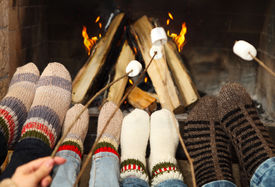 picture of early 20s  - Feet of the family warming at a fireplace with marshmallows on sticks - JPG