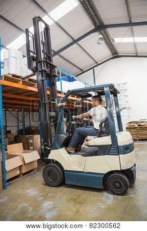 Driver operating forklift machine in a large warehouse