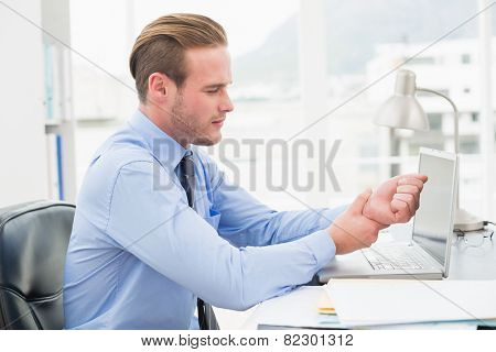 Businessman suffering from wrist pain in his office