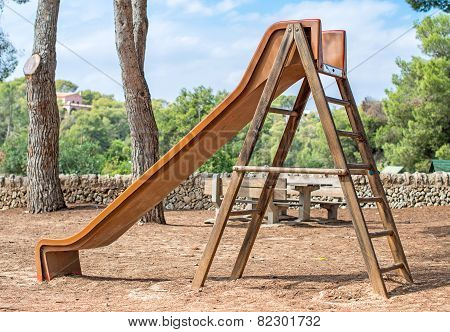 Wooden Children's Slide In The Forest.