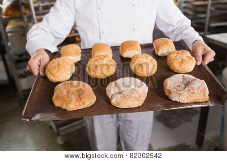 Baker showing tray of rolls in the kitchen of the bakery