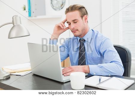 Businessman sleeping at his desk in his office
