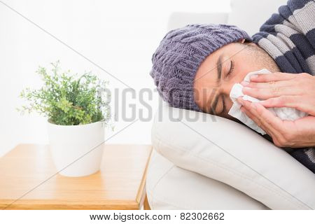 A sick man lying on the sofa in the living room