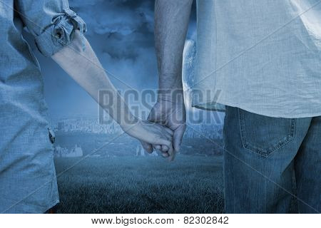 Couple holding hands in park against large moon over city