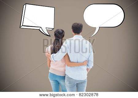 Attractive young couple standing with arms around against grey background with vignette