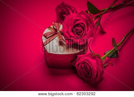 Close up of three roses placed on a gift box on a bright red color background with clear space for headline and text.