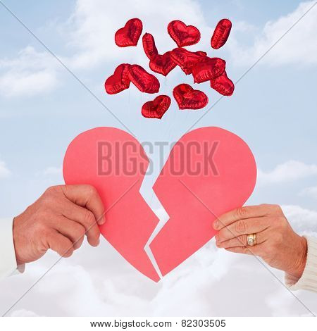 Couple holding a broken paper heart against cloudy sky