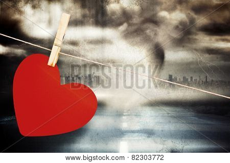 Heart hanging on line against stormy sky with tornado over road