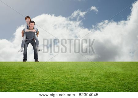 Man giving girl a piggy back against bright blue sky with clouds