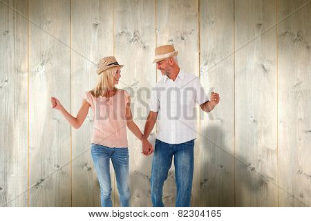Happy couple walking holding hands against pale wooden planks