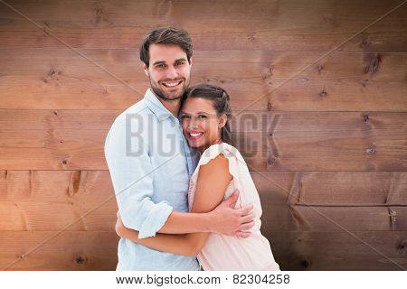 Attractive young couple hugging and smiling at camera against bleached wooden planks background