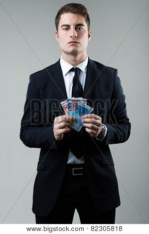 Young Man In Formalwear Holding Money.