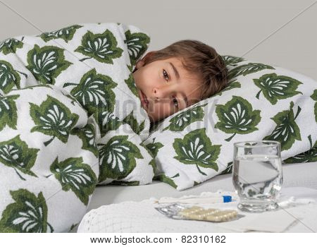 Portrait of sick little boy  in  bed